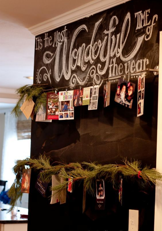 a chalkboard wall with wire and cards hanging on it