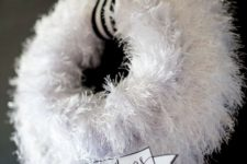 28 a fluffy white wreath with a striped ribbon