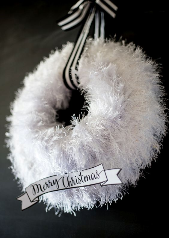 a fluffy white wreath with a striped ribbon
