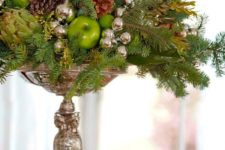 28 a silver stand with oraments, pinecones, evergreens and ggreen apples