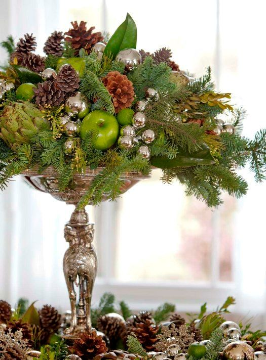 a silver stand with oraments, pinecones, evergreens and ggreen apples