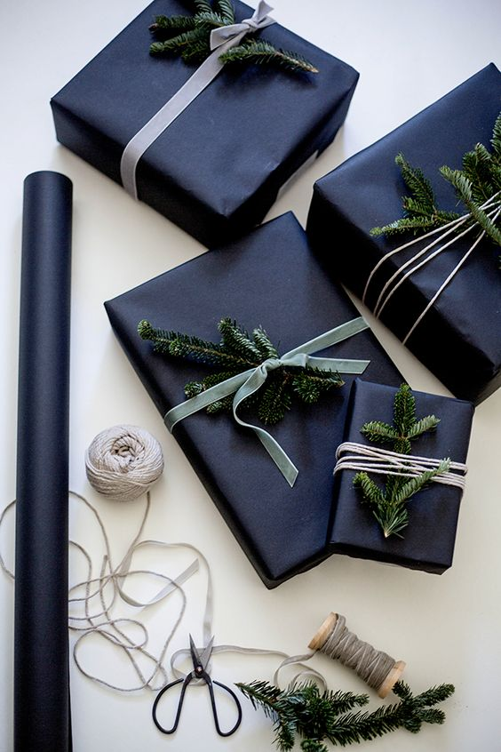 wrap gifts in black and add evergreen sprigs for a laconic yet festive look
