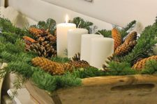 29 a wooden dough bowl with evergreens, pinecones and pillar candles