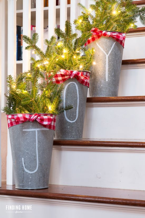 chalk pen galvanized buckets with fir branches and lights