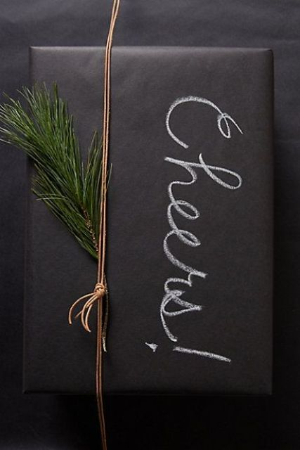 chalkboard gift wrapping with evergreens and chalk writing