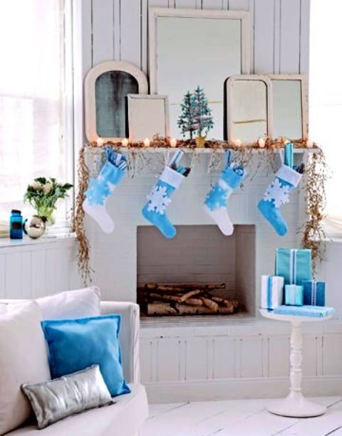 a crispy white and blue Christmas mantel, gifts, stockings and pillows