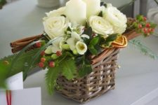 30 a tiny basket arrangement with candles, flowers and cinnamon sticks