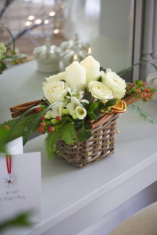 a tiny basket arrangement with candles, flowers and cinnamon sticks