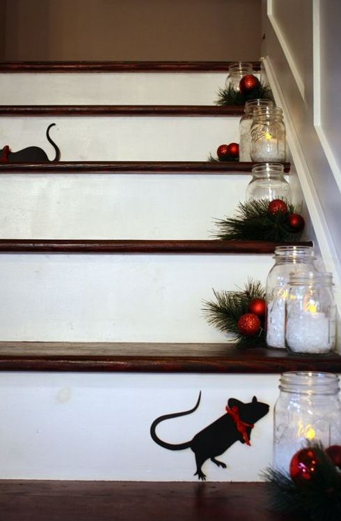 evergreens, small red ornaments, candle holders on the steps