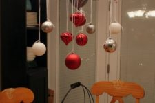 30 place some branches with berries on the chandelier and hang some ornaments