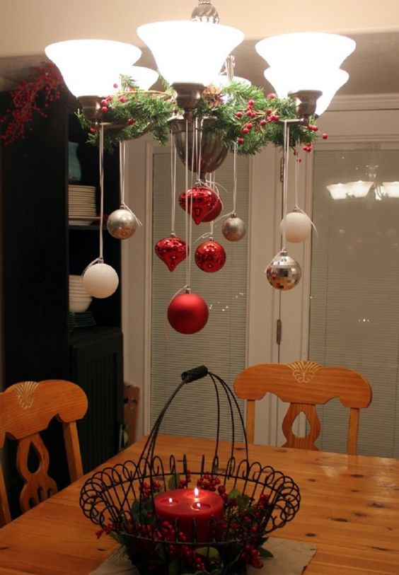 place some branches with berries on the chandelier and hang some ornaments