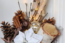 31 a galvanized bucket with logs, pinecones, lights and fabric