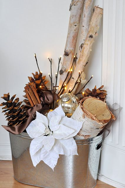 a galvanized bucket with logs, pinecones, lights and fabric