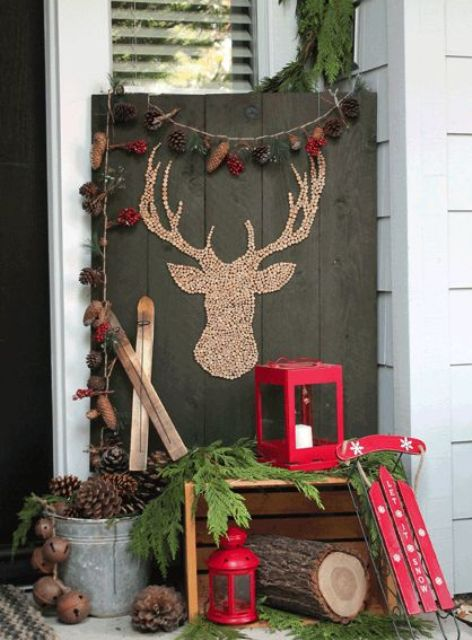 a rustic setup with a crate, a sleigh, a lantern and pinecone decor