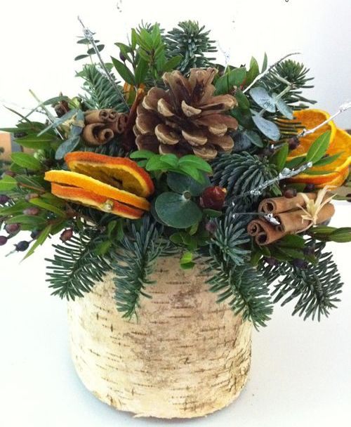 a vase wrapped with bark, evergreens, pincones, citrus and cinnamon sticks