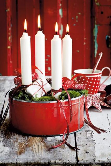 red tin filled with white candles, moss and small gift packs