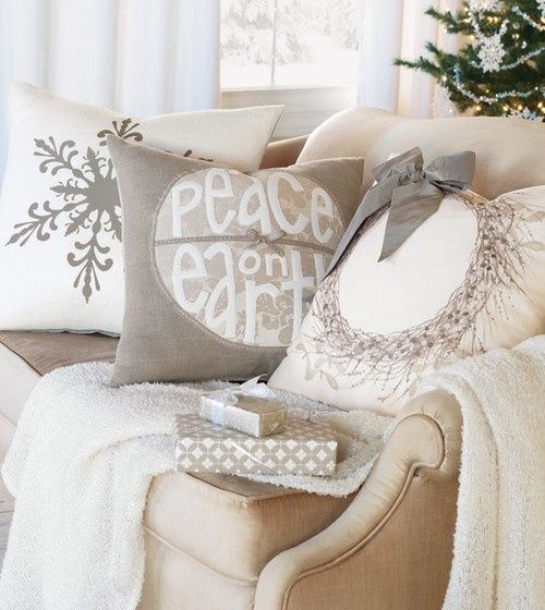 a neutral throw and neutral pillows with winter patterns