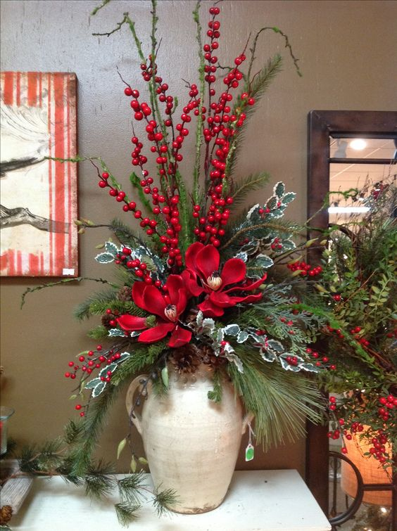 a vintage jug with evergreens, berries, pinecones and flowers is perfect for Christmas entryway display