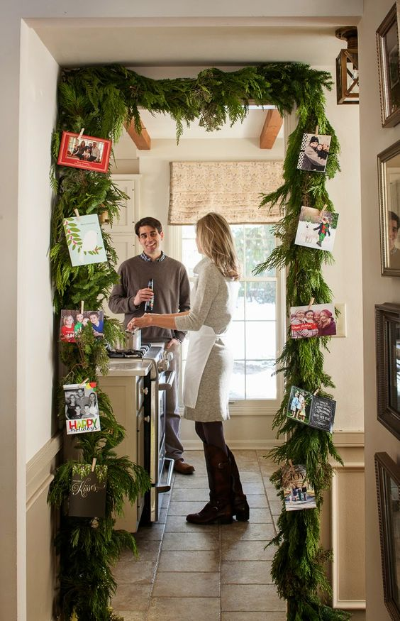 an evergreen garland over the entrance with photos attached