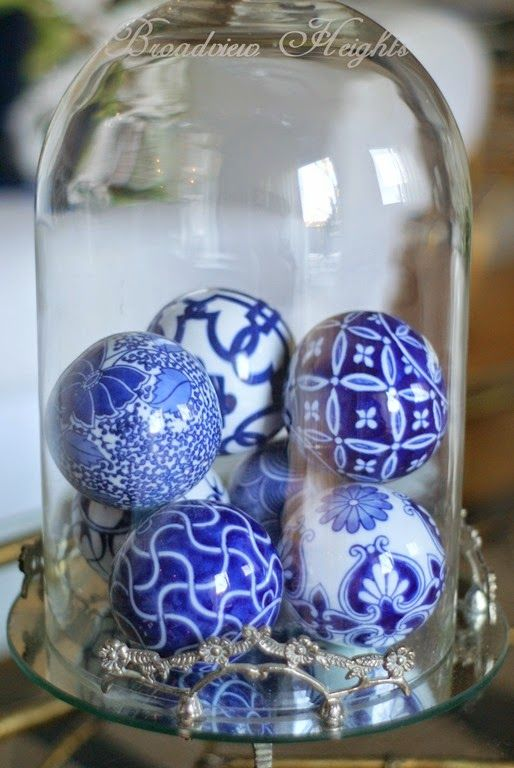 blue and white ornaments in a cloche as a Christmas display