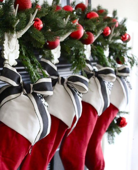 simple red stocking with a white cuff, decorated with striped charcoal and white ribbon, and evergreen sprigs