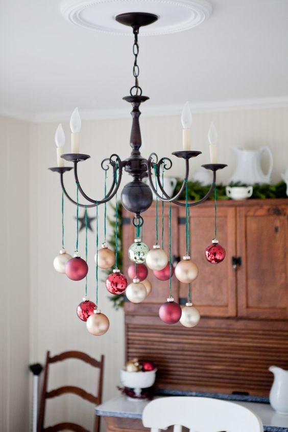 take champagne and red ornaments and hang them on green twine - Christmas Chandelier Decorations