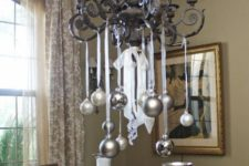 34 silver and metallic grey ornaments hanging on the chandelier