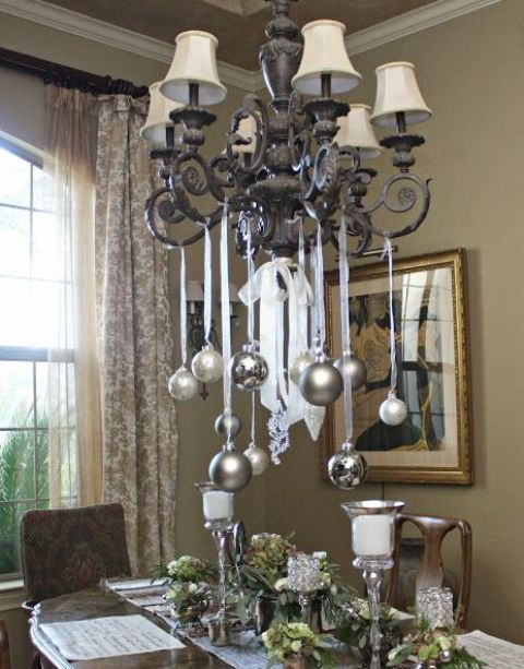 silver and metallic grey ornaments hanging on the chandelier