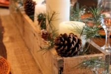 35 rustic wooden box centerpiece with candles, pinecones and evergreens