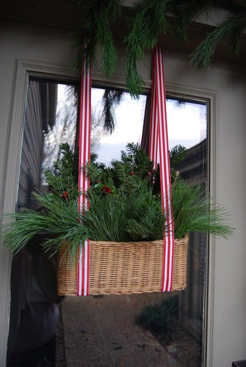 a basket with evergreens and striped ribbon