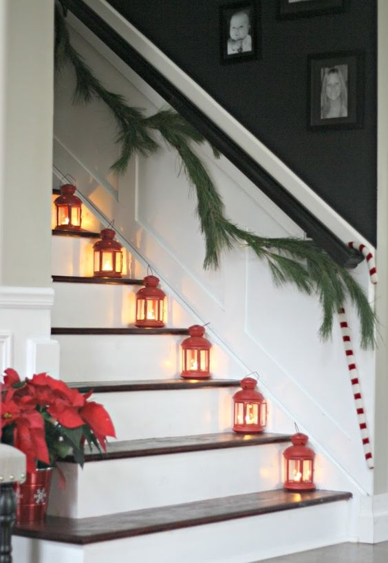 red lanterns placed on the stairs and an evergreen garland