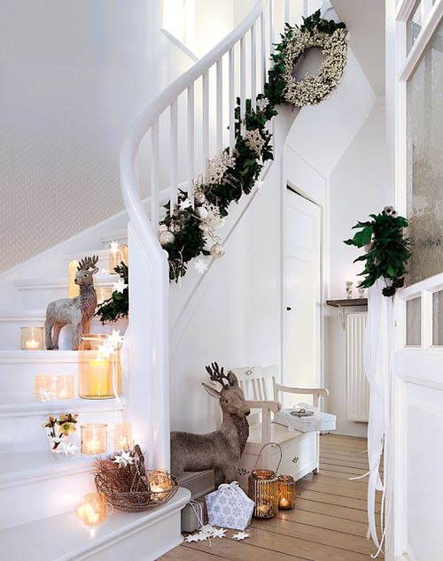 steps decorated with a foliage and paper garland, candles and figures