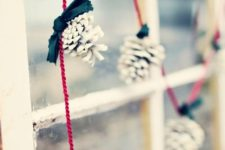 37 white pinecones on red strings for a simple and eye-catchy garland