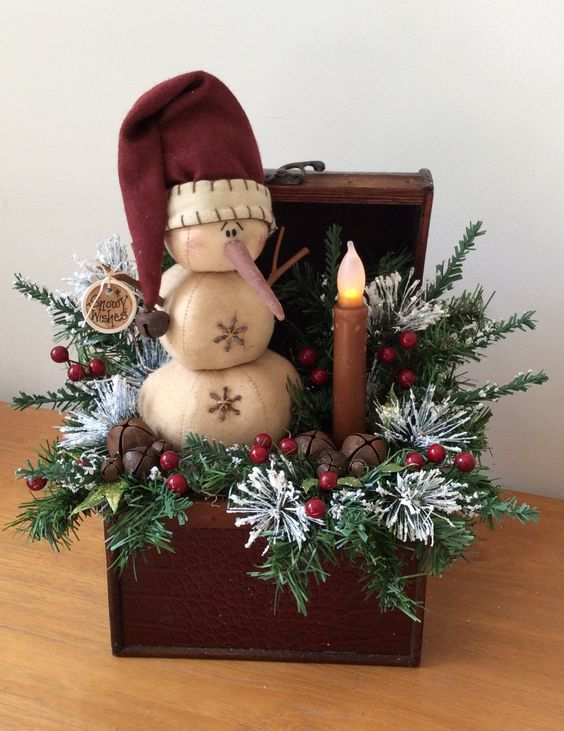 vintage chest with fir branches, a snowman and a candle lamp