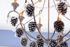 39 hang snowy pinecones on the chandelier