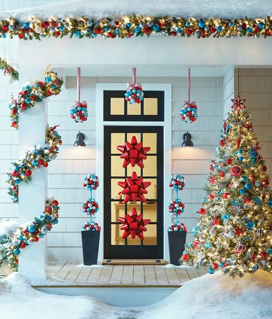 ornament topiaries hanging over the door, garlands and red bows on the door