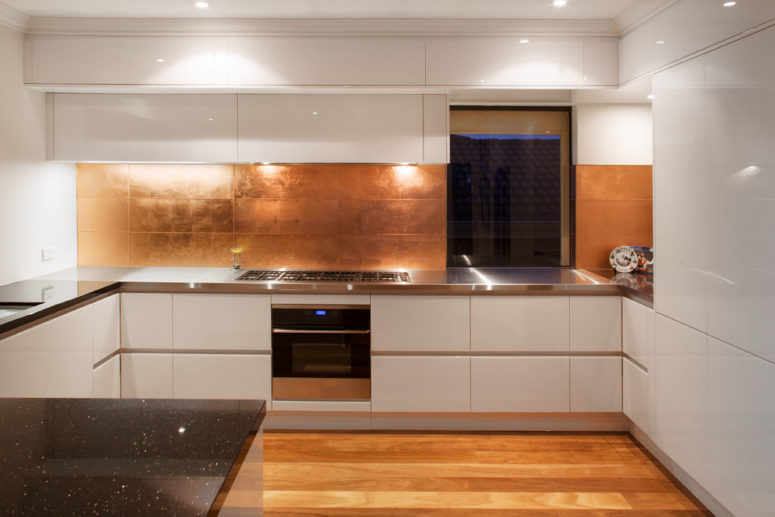 large copper tiles makes the backsplash looks masculine (Retreat Design)