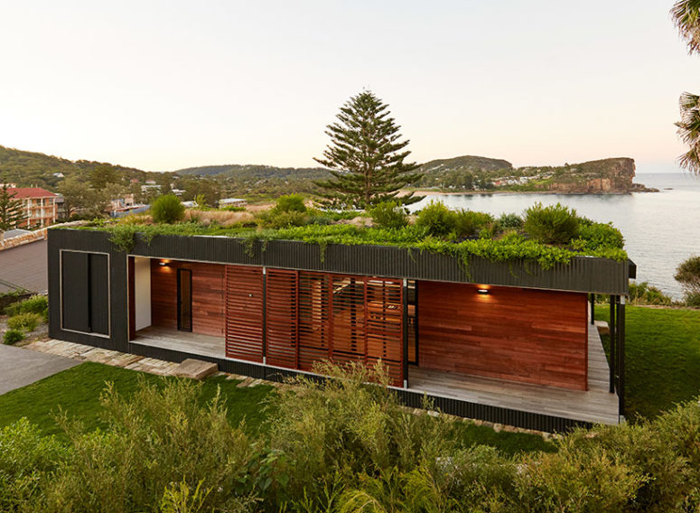 The green roof insulates the home while visually integrating it into the cliff