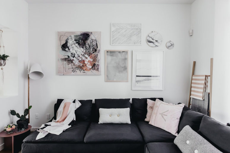 The artworks and blush pillows spruce up the Scandinavian interior of the living room
