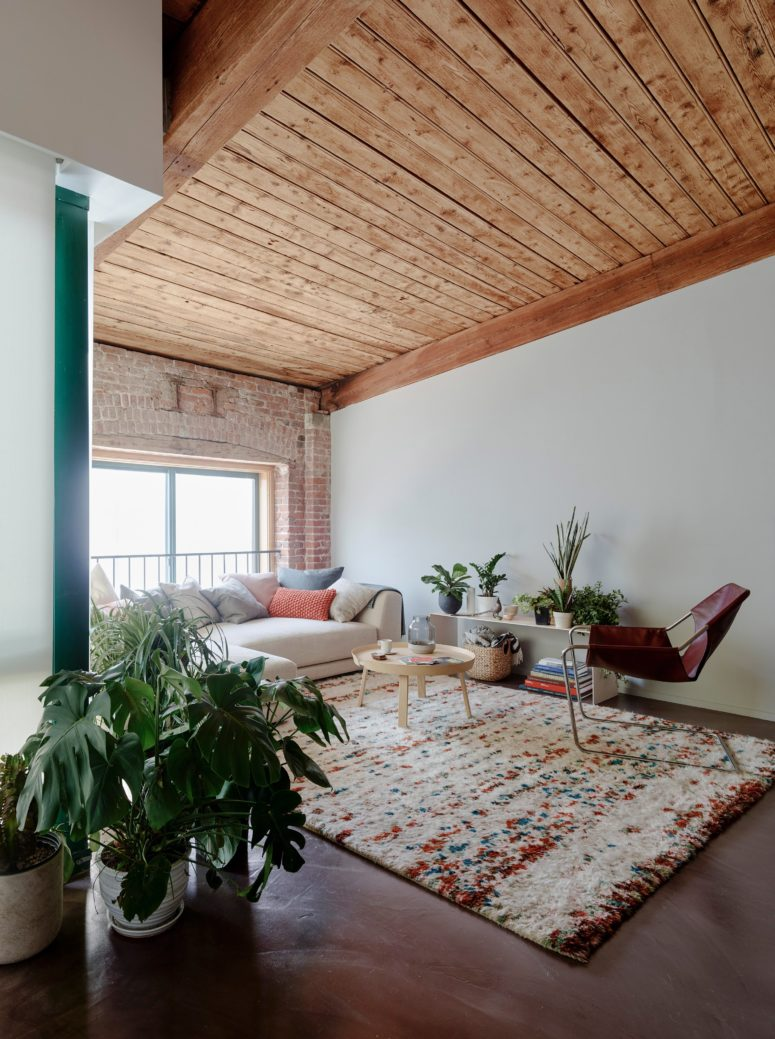The designers saved and highlighted the original features like a brick clad or wooden beams in this living room