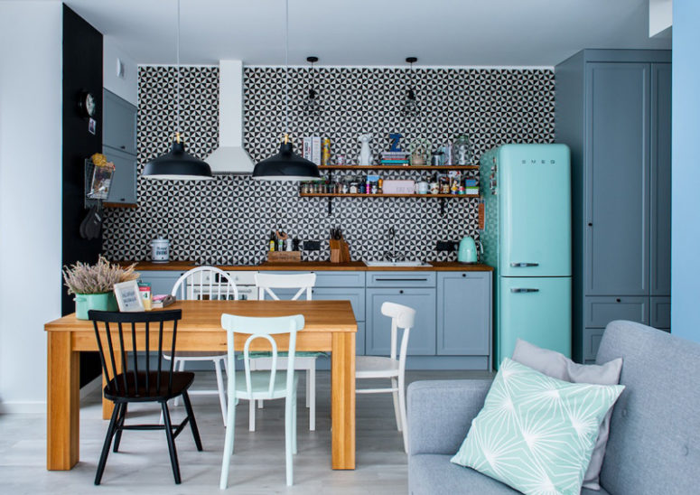 The kitchen has a fantastic graphic tile wall that stands out in the backdrop of pale blue cabinets