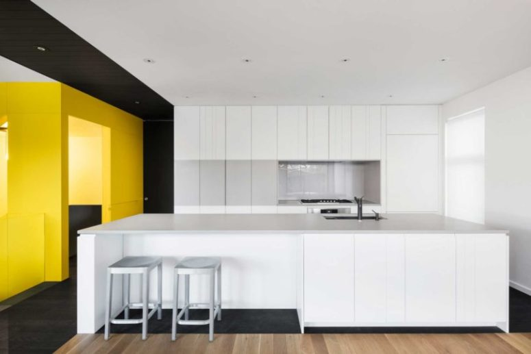 The kitchen is pure white, all the handles and most of appliances are hidden to keep the look minimalist