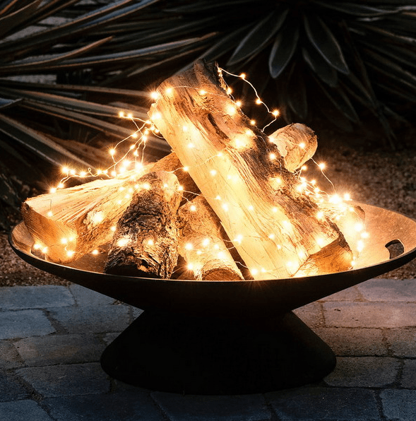 a metal bowl with firewood and string lights to imitate a fire