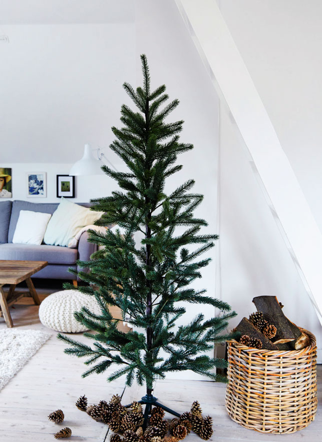 Christmas trees with no decor are a trend, and pinecones and firewood in the basket add a cozy touch