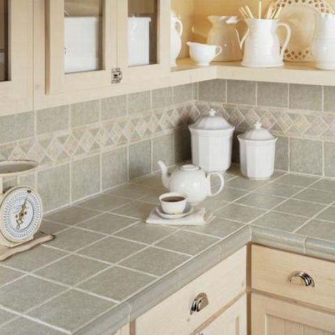 grey tiles on the backsplash and countertops with beige grout