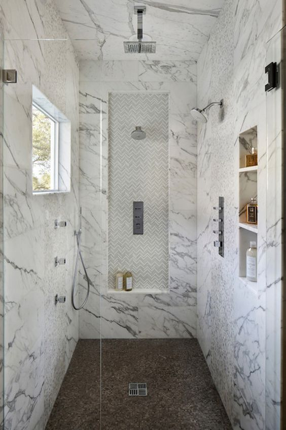 marble walk-in shower with a different floor and built-in shelves