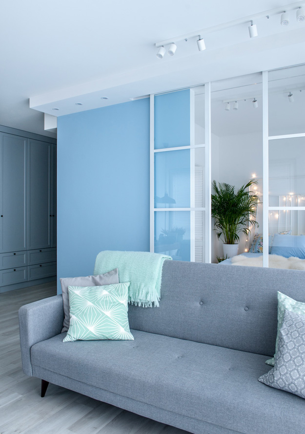 The storage space was made in closed pale blue wardrobes and cabinets to avoid cluttering the space