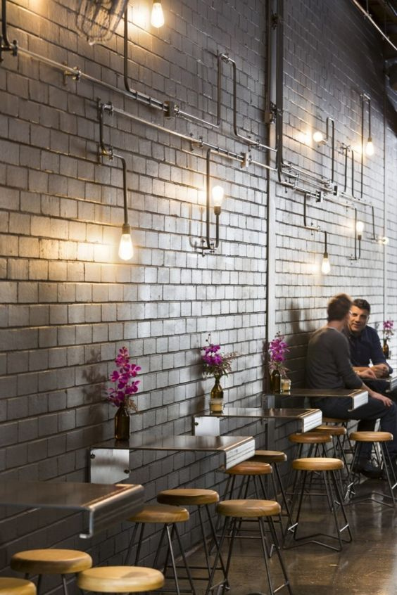 industrial coffee shop with metal tables attached to the walls and exposed pipes with bulbs - Modern Cafe Ideas