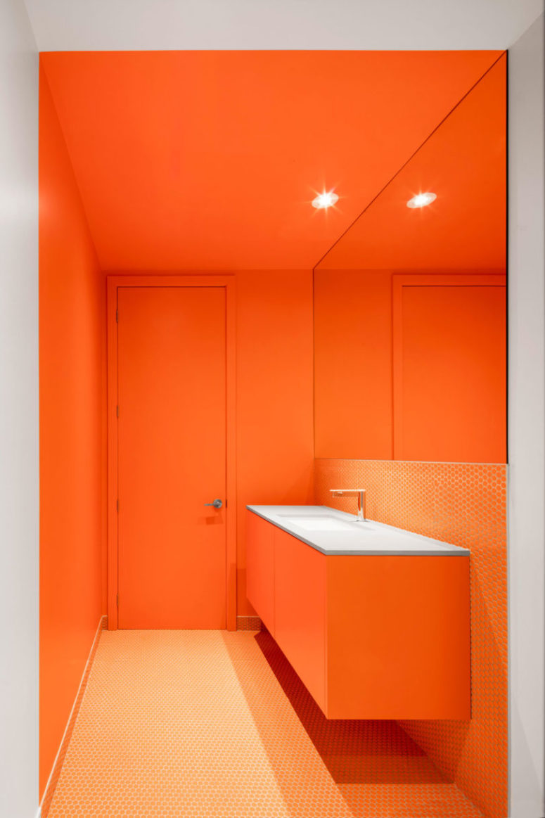 One of the bathrooms features bright orange and penny tiles, the space looks very bold