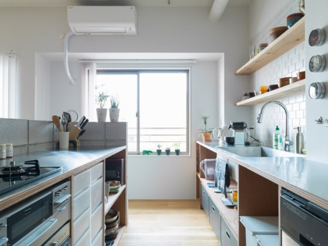 The kitchen is minimalist, with white and warm wood sleek surfaces